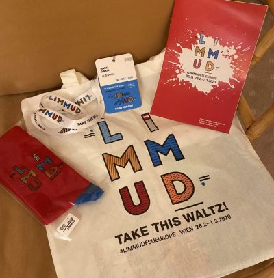Limmud FSU merchandise flat lay including shirt, program and label
